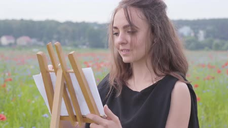 obra prima : Portrait of cute smilling girl painting on the easel tanding on the poppy field. Young woman artist outdoors. Connection with nature. Love nature concept.