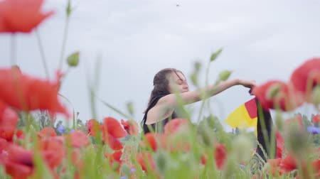 klaprozen : Cute adorable young girl dancing in a poppy field holding flag of Germany in hands outdoors. Connection with nature, patriotism. Leisure in nature. Blossoming poppies. Freedom. Stockvideo