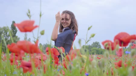 vlčí máky : Cute adorable cute young woman standing in a poppy field holding flag of Germany in hands outdoors. Connection with nature, patriotism. Leisure in nature. Blossoming poppies. Freedom.