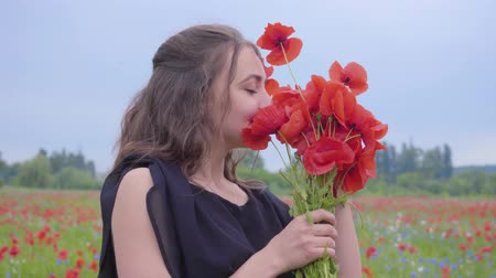 klaprozen : Portrait pretty young woman holding and sniffing bouquet of flowers in hands looking in the camera standing in a poppy field. Connection with nature. Green and red harmony. Leisure in nature.