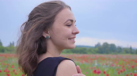 vlčí máky : Portrait of a pretty girl in the poppy field looking away with a happy wide smile. Connection with nature. Green and red harmony. Leisure outdoors, summertime fun