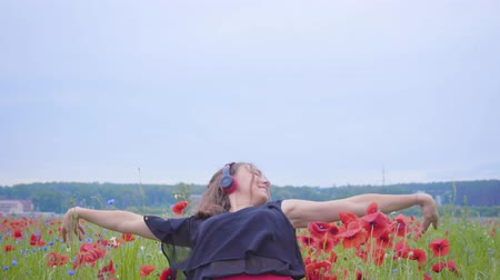 vlčí máky : Pretty young woman wearing headphones listening to music and dancing in a poppy field smiling happily. Connection with nature. Leisure in nature. Blossoming poppies. Freedom. Dostupné videozáznamy