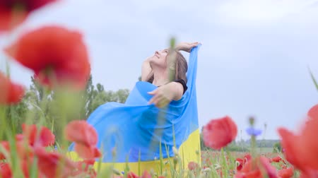 vlčí máky : Cute adorable young woman dancing in a poppy field holding flag of Ukraine in hands outdoors. Connection with nature, patriotism. Leisure in nature. Blossoming poppies. Freedom.