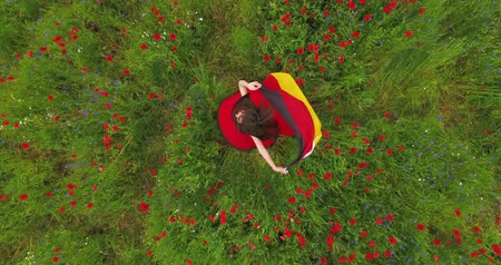 vlčí máky : View from above of young girl dancing in a poppy field holding flag of Germany in hands outdoors. Connection with nature, patriotism. Leisure in nature. Blossoming poppies. Freedom.