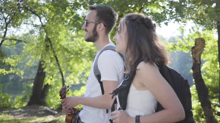restful : Handsome bearded man and young cute girl walking in the forest. Pair of travelers with backpacks outdoors. Leisure couples. Journey to nature.