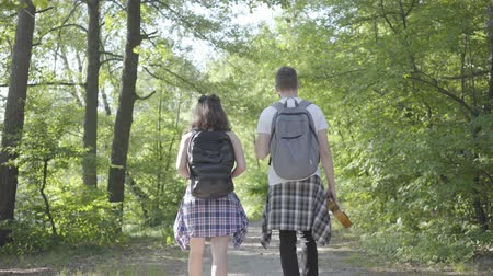ukulele : Portrait man and young cute girl walking in the forest. Pair of travelers with backpacks outdoors. Leisure couples. Journey to nature. Stock Footage