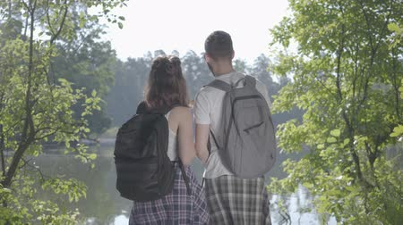 repousante : Happy couple standing on the riverbank in the forest with backpacks pointing away. The young man and woman hiking. Concept of camping. Unity with nature