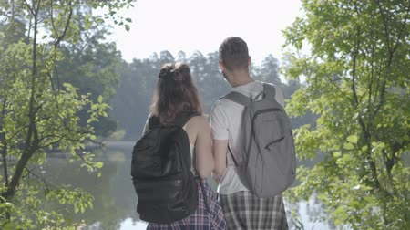 fireside : Portrait couple standing on the riverbank in the forest with backpacks pointing away. The young man and woman hiking. Concept of camping. Leisure couples. Journey to nature. Stock Footage