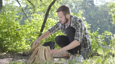 restful : Portrait confident traveler puts firewood for the fire. Handsome man in a plaid shirt prepares to make a fire outdoors. Concept of camping. Leisure and journey to nature. Stock Footage