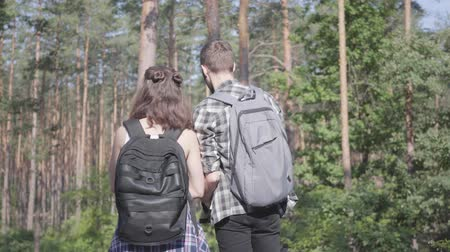 restful : Portrait of guy and young girlfriend walking in the forest. Pair of travelers with backpacks outdoors. Leisure couples. Journey to nature.