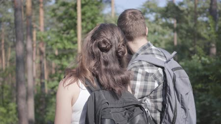 descobrir : Portrait of man and young woman walking in the forest. Pair of travelers with backpacks outdoors. Leisure couples. Journey to nature.