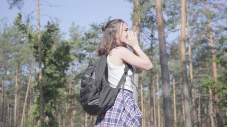 kap : Cute young woman gets lost in the forest, she calling for the help. The girl is in despair, she is alone in the woods. Journey to nature. Stock mozgókép
