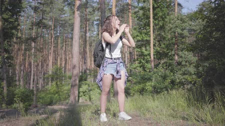 backpacken : Portrait pretty young woman gets lost in the forest, she calling for the help. The girl despair, she is alone in the woods. Journey to nature.