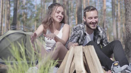 keşfetmek : Portrait handsome young man kindling a fire in the forest while beautiful young woman sitting near. Loving couple resting outdoors. Concept of camping. Leisure and journey to nature. Stok Video