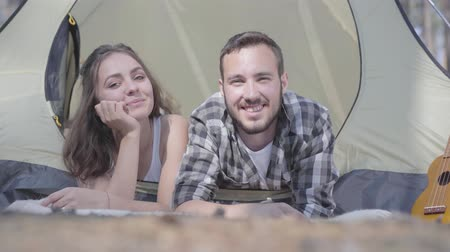 ukulele : The young man pretty young woman lying near each other in the tent in the forest looking in camera smiling. Loving couple having fun outdoors. Concept of camping. Leisure and journey to nature.