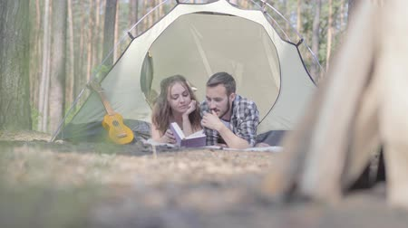 ukulele : Portrait young man pretty young woman lying near each other in the tent in the forest reading the book. Pieces of wood for the fire in the foreground. Loving couple having fun outdoors.