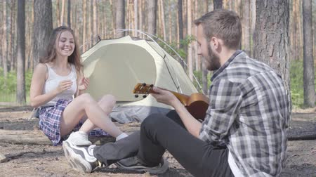 ukulele : The young man playing ukulele at the tent while pretty young woman sitting in front of him clapping hands. Loving couple having fun outdoors. Concept of camping. Leisure and journey to nature. Stock Footage