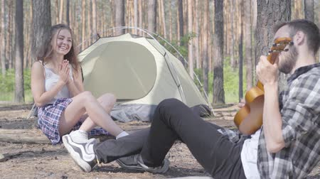 ukulele : Handsome bearded young man playing ukulele at the tent while pretty young happy woman sitting in front of him. Loving couple having fun outdoors. Concept of camping. Leisure and journey to nature. Stock Footage