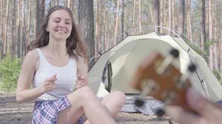 ukulele : Unrecognized man playing ukulele at the tent while pretty young happy woman sitting in front of him. Loving couple having fun outdoors. Concept of camping. Leisure and journey to nature.