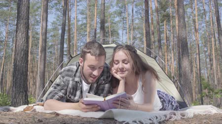 restful : Portrait young man and pretty young woman lying near each other in the tent in the forest reading the book. Loving couple having fun outdoors. Concept of camping. Leisure and journey to nature.