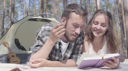restful : Portrait bearded man and cute young woman lying near each other in the tent in the forest reading the book. Loving couple having fun outdoors. Concept of camping. Leisure and journey to nature.