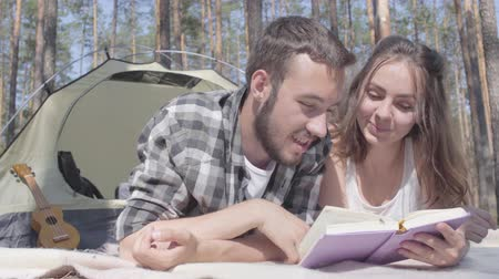 restful : Portrait bearded man and adorable young woman lying near each other in the tent in the forest reading the book. Loving couple having fun outdoors. Concept of camping. Leisure and journey to nature.