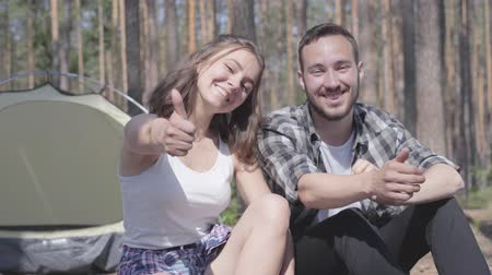 abrigo : Portrait of handsome bearded young man and pretty young happy woman sitting near show thumbs up. Loving couple having fun outdoors. Concept of camping. Leisure and journey to nature.