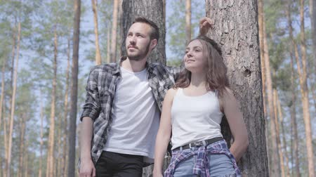 cover up : Portrait of handsome young man and pretty woman looking away standing in the pine forest. Concept of camping. Leisure and journey to nature. Cute couple outdoors. Stock Footage
