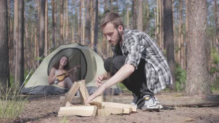 restful : Portrait of bearded handsome man in a plaid shirt prepares firewood to make a fire outdoors. The girl sits in a tent and plays the ukulele or guitar. Concept of camping. Leisure and journey to nature.
