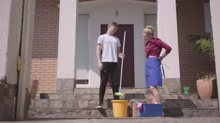 mopping : Positive young woman putting on the apron and the man giving her the mop on the porch of the house. Couple cleaning the house together. Housekeeping household housework and cleaning service concept. Stock Footage