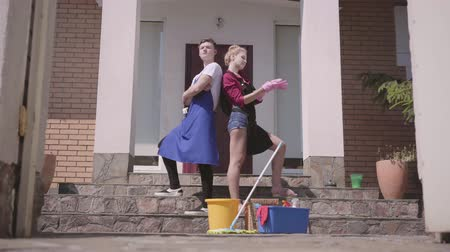 mopping : The gate opening and positive young woman and man in gloves and aprons posing on the porch of the house. Cleaning equipment nearby on the floor. Couple cleaning the house together