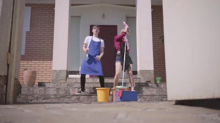 mopping : Cute young woman and man dancing on the porch of the house. Couple cleaning house together. Happy routine life. Housekeeping household housework and cleaning service concept. Slow motion.