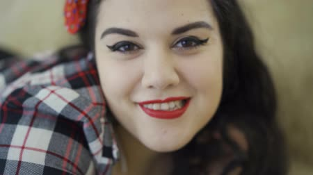 punčocháče : Pretty plus size girl with bright make-up lying on the sofa posing looking in camera. A sensual plump young woman sending air kiss, winking, flirting, attracting Dostupné videozáznamy