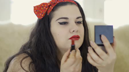 rajstopy : Portrait of attractive young plus size girl doing make-up looking in the mirror close-up. Plump woman painting her lips with bright red lipstick. Preparing for the date