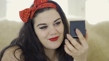 punčocháče : Portrait of attractive young plus size girl doing make-up looking in the mirror close-up. Plump woman preparing for the date. Dostupné videozáznamy