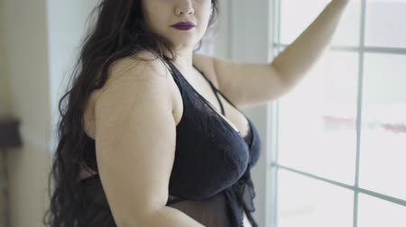 rajstopy : Bohemian sexy plump woman with appetizing shapes standing near window in beautiful underwear and saucy make-up Wideo