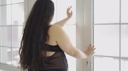 пухлый : Portrait of attractive young plus size girl looking in the window close-up. Back view of plump half dresses pretty woman with long black hair. Leisure indoors