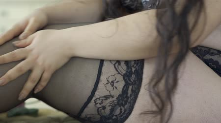 rajstopy : Unrecognized overweight woman in lingerie straightens stocking. Slow motion.