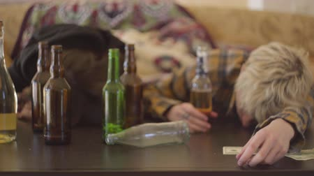 junkie : Young bad looking woman and the man with colored hair lying on the table near empty alcohol bottles. The girl and boy intoxicated. Unhealthy lifestyle. Troubled teens. Addiction problem.