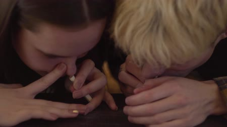 snorting : Close-up woman and the man sniffing cocaine through rolled banknote. Drug use, addiction. Troubled teens. Drug addiction. Stock Footage
