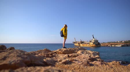 formação rochosa : Beautiful young female tourist in yellow raincoat walking by the rocky beach on the background of picturesque sea, old ship and blue sky. Cyprus. Slow motion.