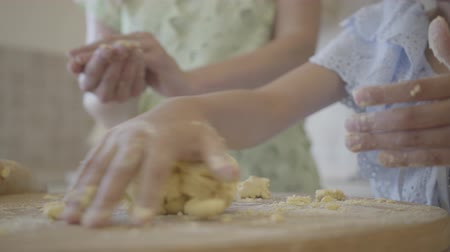 блин : Little daughter under the supervision of her mother rolling out and forming dough for buns. Close up
