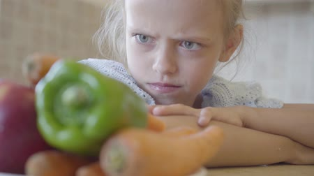 сердитый : Little daughter angrily looking at the plate with vegetables because she does not want to eat them. Close up Стоковые видеозаписи