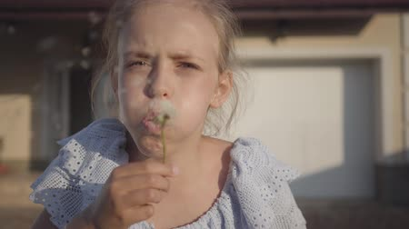 kabartmak : Portrait of a pretty cute little girl blowing a dandelion and looking at the camera smiling. The child spending time outdoors in the backyard. Carefree childhood Stok Video