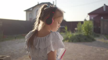 lehkost : Back view of a pretty cute little girl in headphones reading the book sitting on the porch waving hands. The child spending time outdoors in the backyard. Carefree childhood