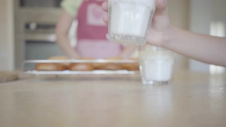 こぼれ : Hand abruptly puts a glass with milk on the table, spilling it on the table close-up. Unrecognizable woman in apron with freshly baked cakes in the background. Lunchtime in a happy family 動画素材