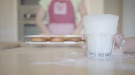 spilled : Childs hand abruptly puts a glass with milk on the table, spilling it on the table. Unrecognizable woman in apron with freshly baked cakes in the background. Lunchtime in a happy family Stock Footage