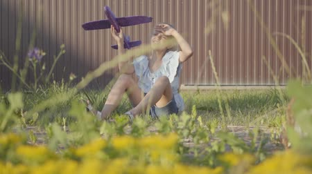 chill out : Cute girl with a toy plane sitting on the green grass in the yard. Girl having fun outdoors. Carefree childhood. Slow motion