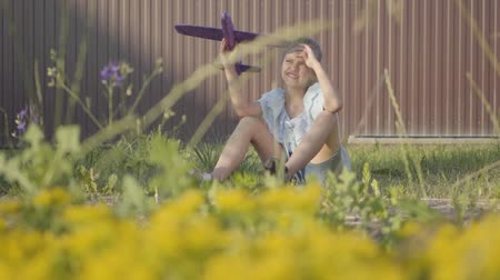 младенчество : Adorable girl with a toy plane sitting on the green grass in the yard. Girl having fun outdoors. Carefree childhood. Slow motion
