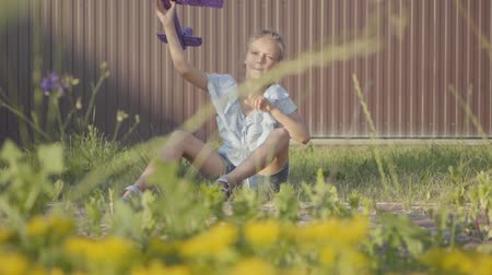 невинность : Portrait of a pretty cute little girl launching the small plane sitting on the grass under the fence. The child spending time outdoors in the backyard. Carefree childhood. Slow motion
